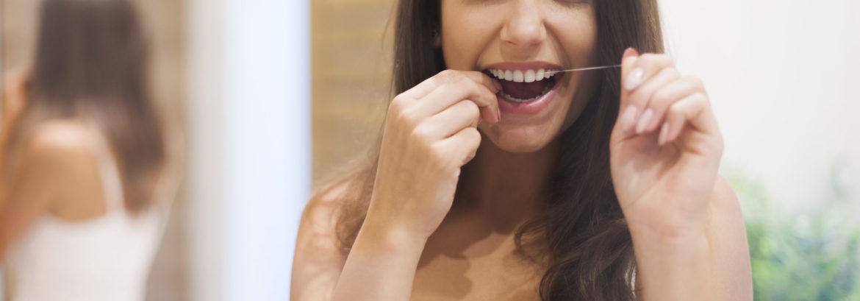 Women Flossing Her Teeth - Clackamas Smiles